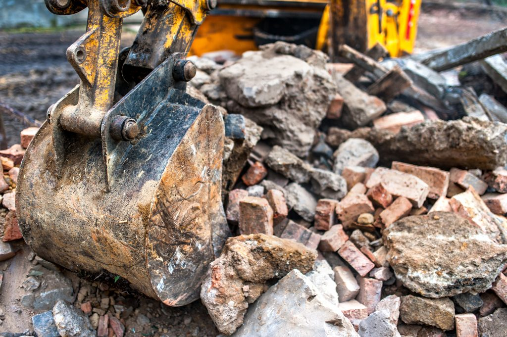 close-up of excavator bucket loading rocks, stones, earth and concrete bricks from demolition site