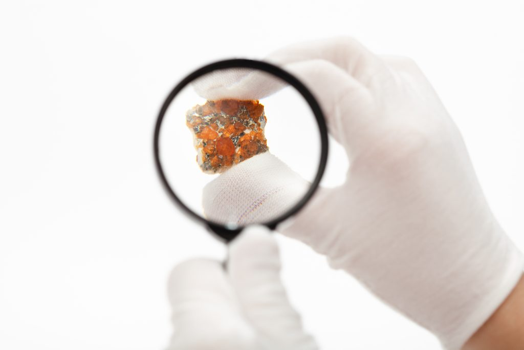 master inspects spessartine garnets with magnifier on white background