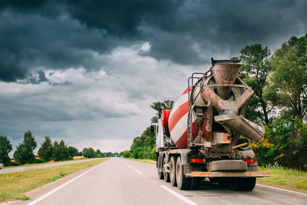 Special Concrete Transport Truck (In-transit Mixer) Unit In Motion On Country Road, Freeway In Europe. Asphalt Freeway, Motorway, Highway. Business Transportation And Development Concept
